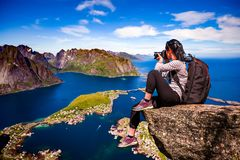 Nature photographer Norway Lofoten archipelago. Nature photographer tourist with camera shoots while standing on top of the mountain. Beautiful Nature Norway Royalty Free Stock Image