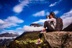 Nature photographer Norway. Nature photographer tourist with camera shoots while standing on top of the mountain. Beautiful Nature Norway Stock Images