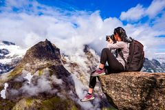 Nature photographer Norway. Nature photographer tourist with camera shoots while standing on top of the mountain. Beautiful Nature Norway Royalty Free Stock Photo