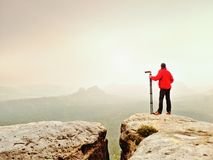 Nature photographer prepare camera to takes impressive photos of misty fall mountains. Tourist photographer. At sharp rocky edge on high view point, misty Royalty Free Stock Photo