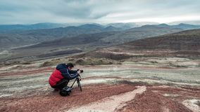 Nature photographer in red mountains. Take picture Royalty Free Stock Photography