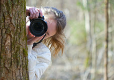 Nature photographer shooting you. Portrait of nature photographer young woman. The girl is shooting you (camera towarded to you) in a spring day sunny forest Stock Images