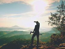 Nature photographer stay at tripod on summit and thinking. Hilly foggy landscape Royalty Free Stock Images