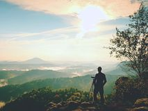 Nature photographer stay at tripod on summit and thinking. Hilly foggy landscape Stock Photos