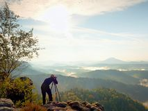 Nature photographer stay at tripod on summit and thinking. Hilly foggy landscape Royalty Free Stock Photos