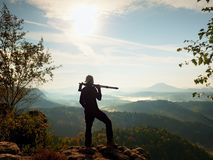 Nature photographer stay at tripod on summit and thinking. Hilly foggy landscape Stock Images