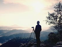 Nature photographer stay at tripod on summit and thinking. Hilly foggy landscape. In first autumnal colors Royalty Free Stock Photography