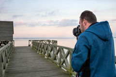 Nature photographer taking photos of the lake at sunset. Professional photographer photographing landscape at the lake at sunset Royalty Free Stock Images