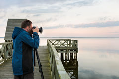 Nature photographer taking photos of the lake at sunset. Professional photographer photographing landscape at the lake at sunset Stock Photos