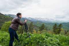 Nature photographer taking photos in the mountains Stock Image