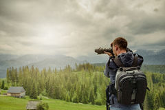 Nature photographer taking photos in the mountains Stock Photography