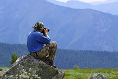 Nature photographer taking pictures. Outdoors during hiking trip on Altai mountains, Siberia Royalty Free Stock Images
