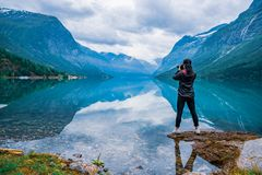 Nature photographer tourist with camera shoots lovatnet lake Bea. Nature photographer tourist with camera shoots Beautiful Nature Norway natural landscape Royalty Free Stock Photo