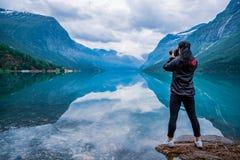 Nature photographer tourist with camera shoots lovatnet lake Bea. Nature photographer tourist with camera shoots Beautiful Nature Norway natural landscape Stock Images