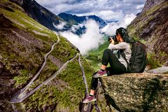 Nature photographer tourist with camera shoots while standing on. Top of the mountain. Troll`s Path Trollstigen or Trollstigveien winding mountain road in Stock Images