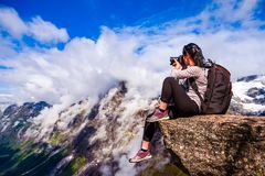 Nature photographer Norway. Nature photographer tourist with camera shoots while standing on top of the mountain. Beautiful Nature Norway Royalty Free Stock Images