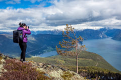 Nature photographer. Tourist with camera shoots while standing on top of the mountain. Beautiful Nature Norway Royalty Free Stock Photos