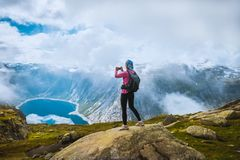 Nature photographer tourist near Norway lake. Nature photographer tourist with camera shoots while standing on top of the mountain. Beautiful Norway Nature Stock Images