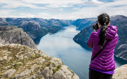 Nature photographer. Tourist with camera shoots while standing on top of the mountain. Beautiful Nature Norway Preikestolen or Prekestolen Royalty Free Stock Photos