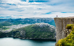 Nature photographer. Tourist with camera shoots while standing on top of the mountain. Beautiful Nature Norway Preikestolen or Prekestolen Stock Image