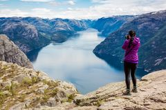 Nature photographer Beautiful Nature Norway Preikestolen or Prek. Nature photographer tourist with camera shoots while standing on top of the mountain. Beautiful Royalty Free Stock Photos