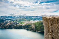 Nature photographer Beautiful Nature Norway Preikestolen or Prek. Nature photographer tourist with camera shoots while standing on top of the mountain. Beautiful Royalty Free Stock Image