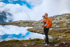 Nature photographer tourist near Norway lake. Nature photographer tourist with camera shoots while standing on top of the mountain. Beautiful Norway Nature Stock Photo