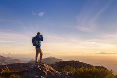 Nature photographer traveler taking photo of beautiful landscape. From top of the mountain Stock Images
