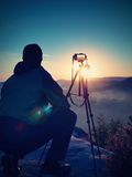 Nature photographer with tripod and camera on cliff and thinking Stock Photography