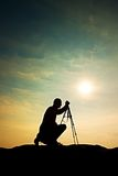 Nature photographer with tripod on cliff and thinking. Dreamy fogy landscape, misty sunrise in valley below Royalty Free Stock Photo