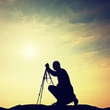 Nature photographer with tripod on cliff and thinking. Dreamy fogy landscape, misty sunrise in valley below Royalty Free Stock Photos