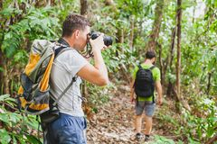 Nature photographer in tropical jungle, group of tourists hiking in the forest stock photography