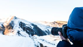 Nature photographer in winter mountains. Make shot Royalty Free Stock Photography