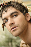 Nature Portrait. Close-up portrait of beautiful young man in nature with leaves and branches in his hair Stock Photos
