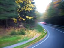 Nature road artistic motion blur. A road through wood with artistic motion blur - turning left. Nature road artistic motion blur photo is made from the bus stock image