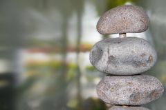 Nature - rocks on a pole close-up to side of image against bokeh blurred green nautral background - room for copy stock images