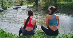 At nature on the rooftop of river two ladies take a fresh air after a hard workout exercises they enjoy the time. Together stock video
