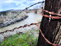 Nature with Rust. A photograph of a rusted barbed wire fence that frames a small river stock photo