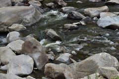 Rushing water over stream beds through the mountain stock photo