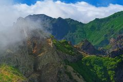 Nature scene of green mountains against cloudy blue sky. View from Pico do Ariero on Portuguese island of Madeira stock images