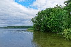 Nature scene of a lake against cloudy sky. Nature scene of a lake and green trees on the coast against cloudy sky stock photography