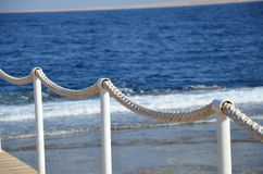 Nature.sea.pebble beach.wave.bridge.white rope Stock Image