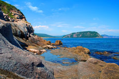 Beautiful sea landscape with a rock and the bright blue sky Royalty Free Stock Photos