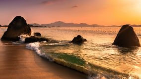 Nature Seascape with Boulders on Sandy Beach and Surging Waves at Sunrise royalty free stock photography
