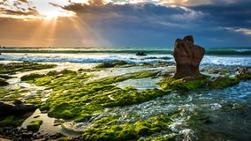 Nature Seascape with Exotic Boulder and Green Moss Covered Rocks in The Morning Sunshine stock image