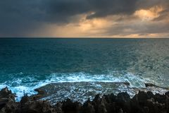 Nature Seascape with Rough Rocks, Waves, Dark Clouds and Sky during A Storm at Sunrise royalty free stock images