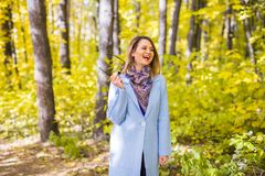 Nature, season and people concept - young woman laughing at the autumn park royalty free stock image