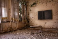 Nature is taking back this classroom!. Abandoned classroom in a european school. The windows are closed for ever and and nature will find its way back into the stock photography