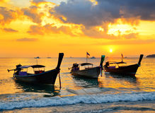 Traditional thai boats at sunset beach Stock Photo