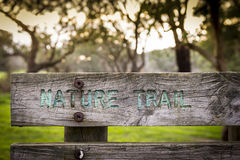 Nature Trail Sign. Old wooden panel sign with Nature Trail text engraved on it Royalty Free Stock Images